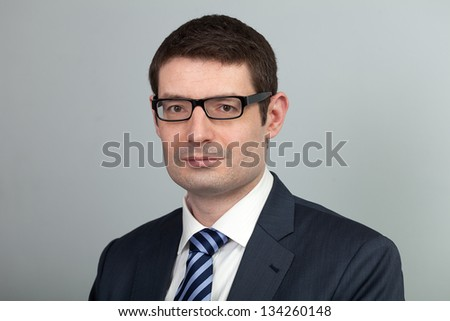 A head and shoulders shot of a black framed eyeglasses wearing 40 year old business man in a suit and shirt with blue tie. - stock photo