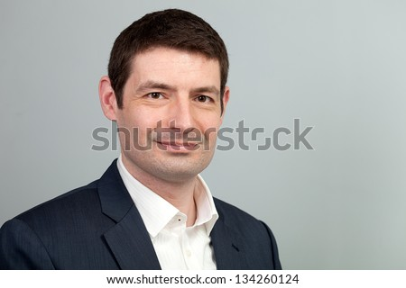 A head and shoulders shot of a 40 year old business man in a suit and shirt with no tie and open collar. - stock photo