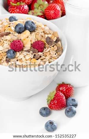 A healthy bowl of muesli with fresh berries on white background.