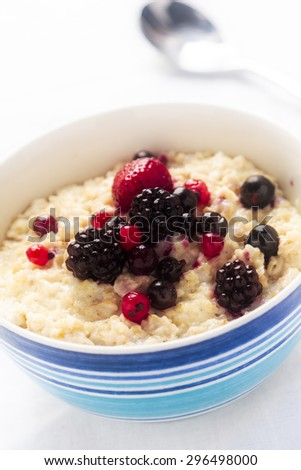 A healthy bowl of porridge served with fresh berries with soft focus applied - stock photo