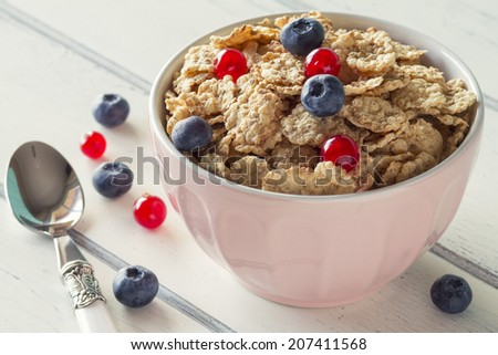 A healthy breakfast: cereals with blueberries and red currants on a white wooden table. Vintage Style.