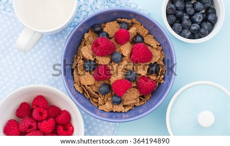 A healthy breakfast of bran flake cereal, raspberries and blueberries. View from above looking down onto the breakfast table. - stock photo