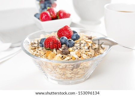 A healthy breakfast of muesli with fresh berries on white background.