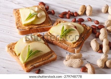 A healthy breakfast: toast with fresh apple and peanut butter on the table. horizontal  - stock photo