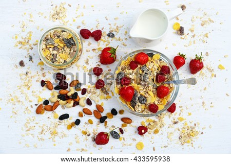 A healthy breakfast with cereal muesli, milk, nuts and berries - stock photo