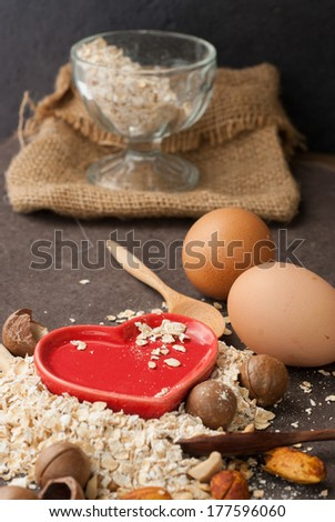 A Healthy Dry Oat meal with nut and Red heart in a wooden spoon on Black background - stock photo