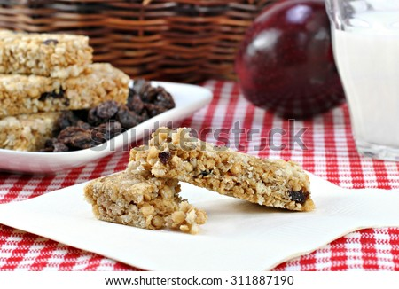 A healthy granola bar, raisin, apple and milk snack.