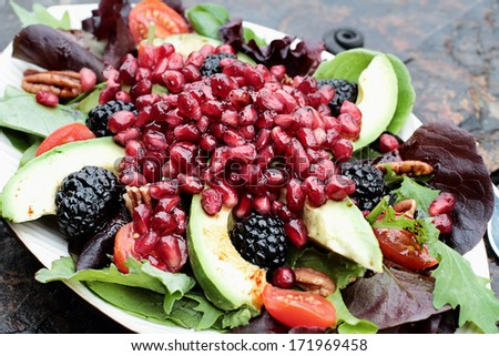 A healthy salad with pomegranate, avocado, tomatoes, almonds and argula lettuce over a rustic background.  - stock photo