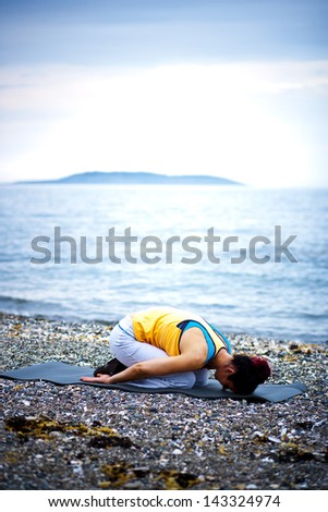 A healthy young woman sitting in childs pose on a yoga mat - stock photo