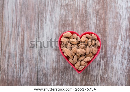 A heap of almonds in a red heart shaped bowl on wood background from above - stock photo