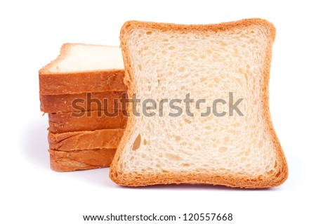 A heap of bread slices and one slice like a copy space, leaning on the heap - isolated on white - stock photo
