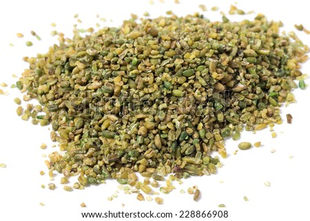 A heap of frikeh or freekeh grains on a white background. The cereal is made from immature, green wheat which is fire-roasted to make a healthy, low-glycemic-index food high in protein and minerals, - stock photo
