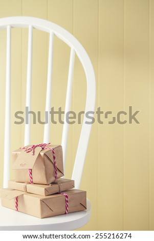 A heap of paper parcels wrapped tied with tags. Some gift boxes wrapped with paper kraft and tied with red & white baker's twine on a white windsor chair beside a yellow wainscot. - stock photo