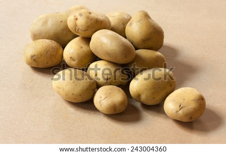 A heap of potatoes on a wooden board - stock photo