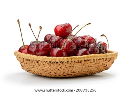 A heap of red fresh and natural cherries in a rattan basket