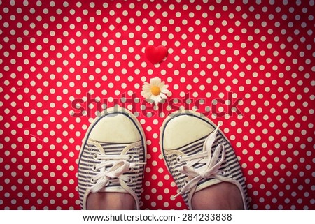 A Heart, a daisy and striped pumps on red polka dots - stock photo
