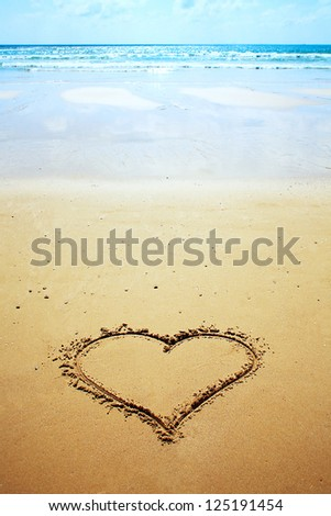 A heart drawn in the sand on the beach. Romantic design element. - stock photo