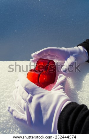 A heart in the snow which is covered by two hands - stock photo