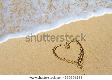 A heart is drawn in the sand on the Hawaii beach showing an image of white sand, water, waves, and the symbol for love. This would be a great image for a honeymoon, valentines day, or love design.
