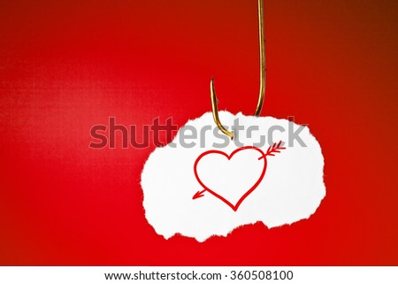 A heart pierced with an arrow drawn on white piece of paper hanging on a fishing hook over red background.  - stock photo