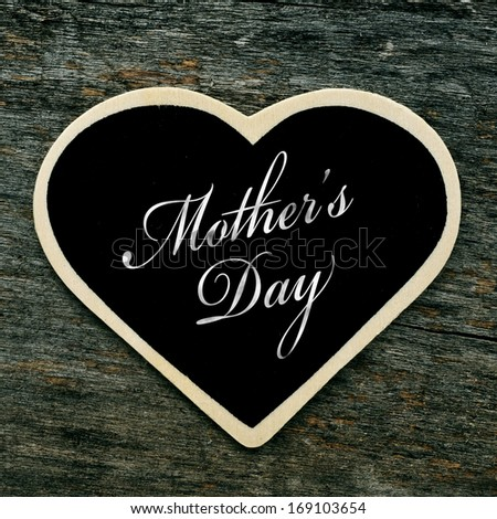 a heart-shaped blackboard with the text mothers day written in it on an old wooden surface - stock photo