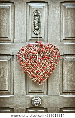 A heart shaped christmas wreath on a wooden front door - stock photo