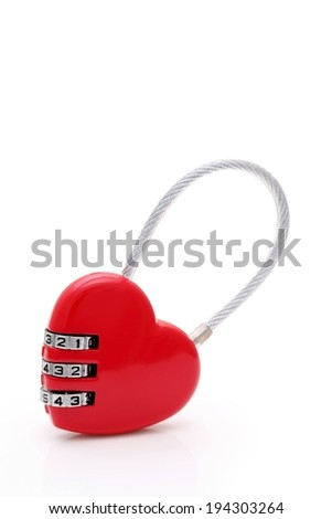 A heart shaped combination lock on a white surface. - stock photo