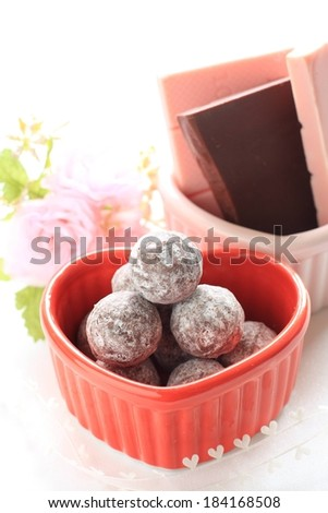 A heart shaped dish holds chocolate balls with bars in the back. - stock photo