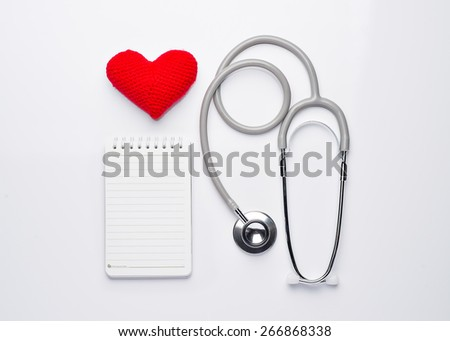 A heart with a stethoscope and note isolated on white background. View from the top - stock photo