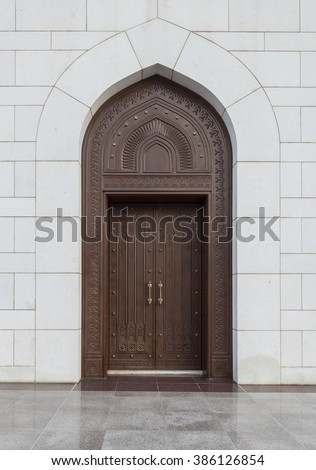 A heavily handcrafted wooden door with intricate Islamic design. Front facade. - stock photo