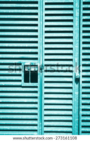A heavy duty metal gate as a background image in blue monochrome - stock photo