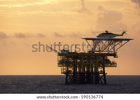A helicopter on top of a offshore oil-platform for transporting roughnecks to nearby rigs - stock photo
