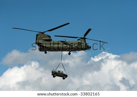 a helicopter transports a jeep - stock photo