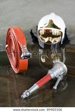 A helmet, a firehose and a nozzle on the floor in a fire station used by firefighters