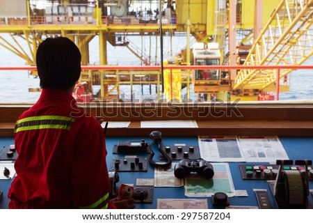 A helmsman on the bridge of a supply vessel nearby an offshore oil-rig - stock photo