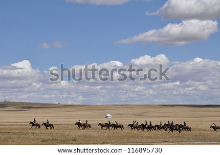 A herd of horse riders on  th pasture in autumn,inner mongolia,China.