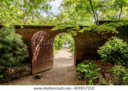 A hidden gate is opening up to a beautiful English style garden with rounded hedges, beautiful flowers, & symmetric type design, with sand & brick sidewalks and footpaths to enjoy the scenic view. - stock photo