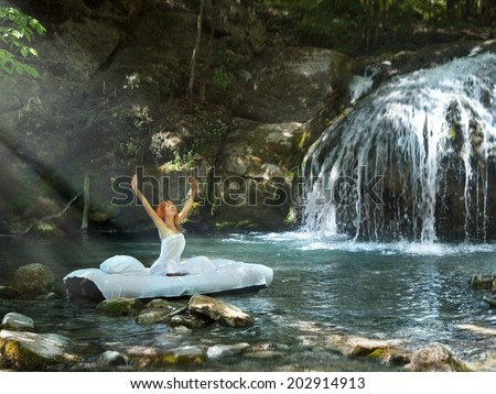 A hidden place. Sleeping woman in deep forest lies on matrace. waterfall on back