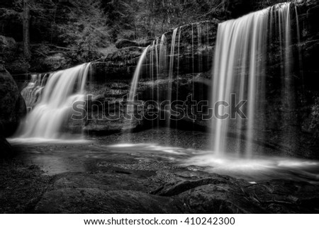A hidden waterfall  in Hocking Hills Ohio in black and white. Found near the famous Cedar Falls behind a large slump block. - stock photo