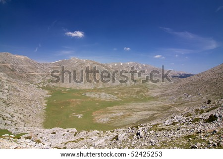 A high-altitude alpine plateau, confined by high summits of mountain Giona in central Greece