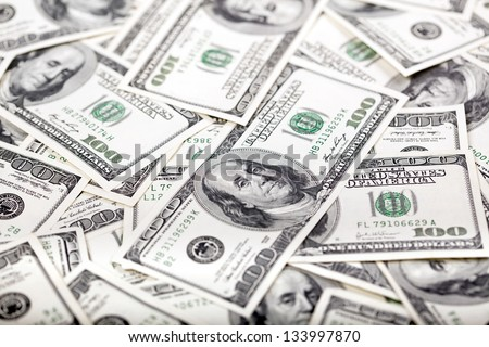 A high angle view close up shot of a very large amount of 100 US$ money notes in a bulky mess. - stock photo
