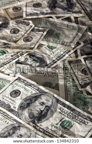 A high angle view of a very large amount of crumpled 100 US$ money notes in a bulky mess, with warm & contrasty lighting. - stock photo