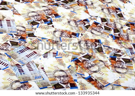 A high angle view of a very large amount of 100 NIS (New Israeli Shekel) money notes spreaded in a messy manner. - stock photo