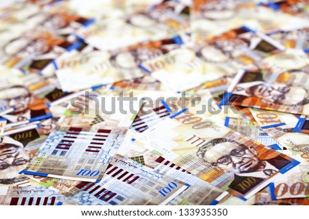 A high angle view of a very large amount of 100 NIS (New Israeli Shekel) money notes spreaded in a messy manner. Very shallow depth of field. - stock photo