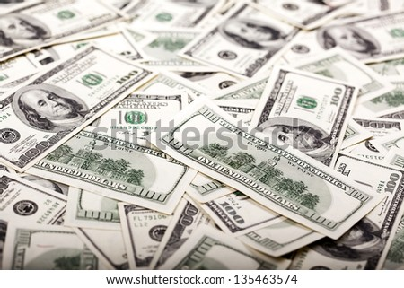 A high angle view of a very large amount of 100 US$ money notes in a bulky mess. On the front there is a note showing its reverse side, depicting the Independence Hall. Very shallow depth of field. - stock photo