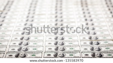 A high angle view of a very large amount of 100 US$ money notes, with a very shallow depth of field. - stock photo