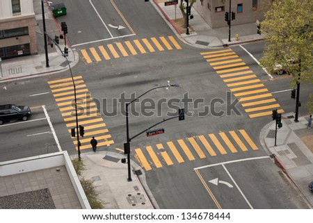 A high angle view of an almost empty street intersection, with yellow cross walk markings, traffic signal lights, and curb cuts, in San Jose, California. - stock photo