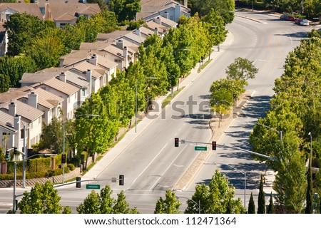 A high angle view of tract homes along a wide street in San Jose, California. - stock photo