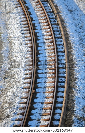 a high angle view of train track sprinkled with dusting snow