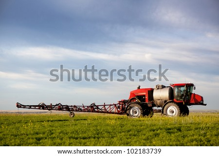 A high clearance sprayer on a field  in a prairie landscape